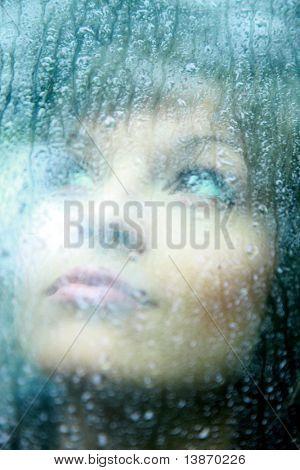 Traurige junge Frau und ein Regentropfen