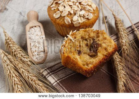 Fresh muffins with oatmeal baked with wholemeal flour rye flour and ears of rye grain concept of delicious healthy dessert or snack