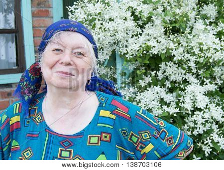 Smiling elderly woman in a kerchief on background of white flowers in your garden.
