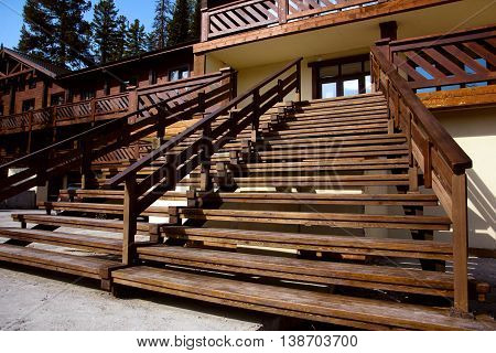 A wide wooden staircase at the entrance to the house. Large terrace.