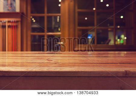 Empty wooden deck table over interior restaurant and bar bokeh background for product montage display