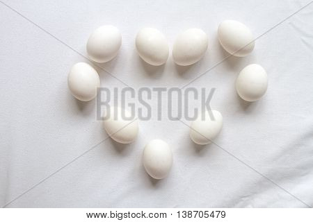 White eggs in heart shape on white tablecloth