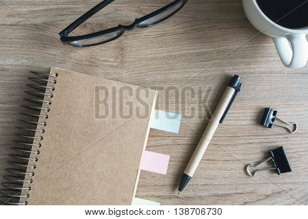 Cup of coffee with blank notebook and notepaper on wooden desk Top view
