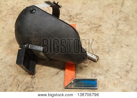 Welding Mask on Dirty Floor in Manufacturing Workshop.