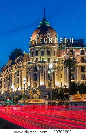 Nice France - April 20 2016: Light trails in front of hotel Negresco at night. Negresco is the famous luxury hotel on the Promenade des Anglais in Nice baie des Anges a symbol of the Cote d'Azur or the French Riviera