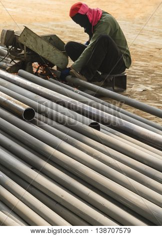Worker cutting steel by cutting fiber in construction factory.