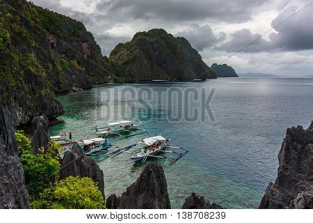 Boats parked in a rocky bay of turquoise water in the Philippines
