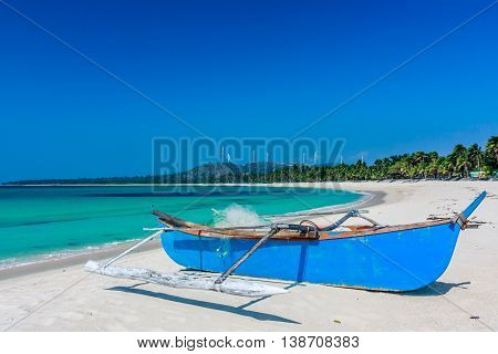 Blue boat on a deserted white sand beach and windmills in the Philippines