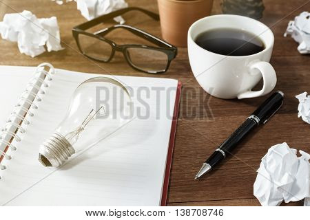 Crumpled paper balls with cup of coffee and notebook on wooden desk creative writing concept
