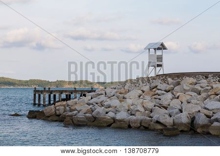 White lifeguard over rock on the seacoast, natural landscape background