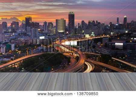 Opening wooden floor, City background and highway intersection with sunset sky