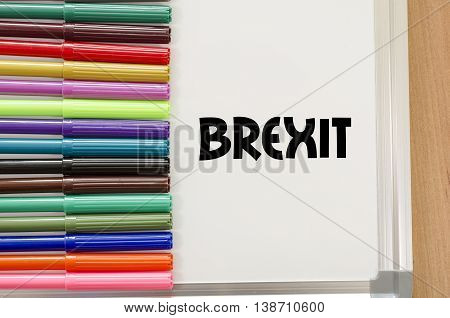 Brexit written on whiteboard over wooden background