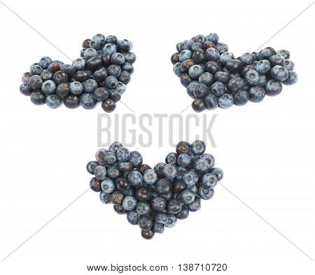 Heart shape made of bilberries isolated over the white background, set of three different foreshortenings