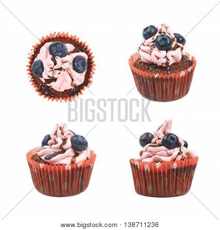 Single chocolate muffin coated with the pink cream frosting and fresh bilberries, composition isolated over the white background, set of four different foreshortenings