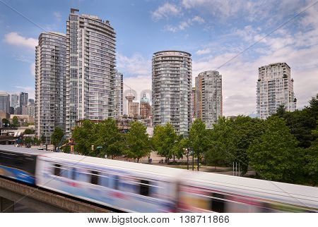 Vancouver Growing Skyline. Modern towers and heritage buildings line Vancouver's skyline behind a rapid transit line. British Columbia, Canada.