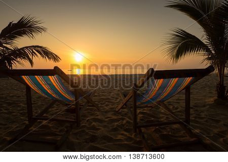 Couple of sun loungers on the beach during sunset.