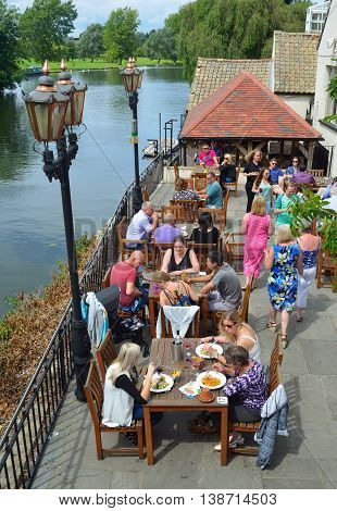 St Neots, Cambridgeshire, England - July 16, 2016: People eating out by the riverside in the sunshine.