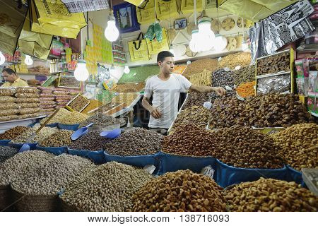 MARRAKESH - JULY 09: Unknown man trades a dried fruits in a market (souk), July 09, 2013 in a Marrakesh, Morocco. The market is one of the most important attractions of the city Marrakesh, Morocco