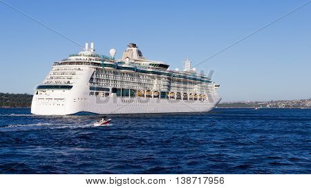 Sydney - February 25 2016: a huge sea liner Radiance of the seas came from Sydney harbor cruise and a small sailing boat near February 25 2016 Sydney Australia