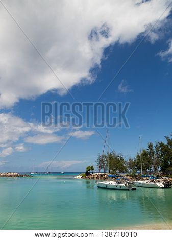 La Digue - 9 November 2014: Yachts standing in port and beautiful reflection in sea water and beautiful weather November 9 2014 La Digue Seychelles