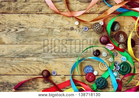 vintage buttons and multicolored ribbons lie on old wooden table