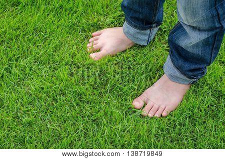 Bare feet of Asian child on green grass