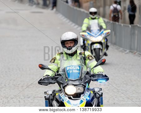 STOCKHOLM - JUL 02 2016: Two swedish police officers on motorcycles on cobblestone checking the security in the Women's ITU World Triathlon series event July 02 2016 in Stockholm Sweden