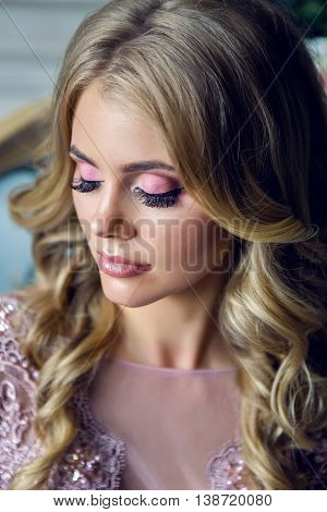 young sexy blonde girl in pink lace dress looks up and smiles