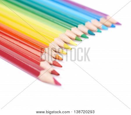 Multiple colorful color pencils composition arranged in a line to form a rainbow gradient, composition isolated over the white background, close-up crop fragment