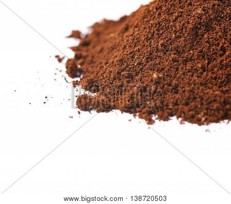 Pile of the ground coffee flakes isolated over the white background, close-up crop composition