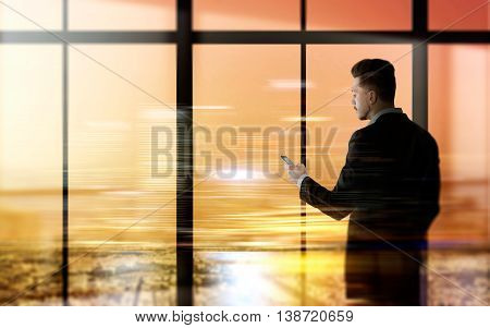 Side view of young businessman using smartphone against panoramic window with city view