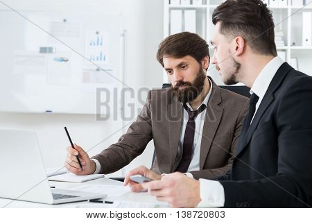 Concentrated businesspeople working together at modern office desk with laptop and other items