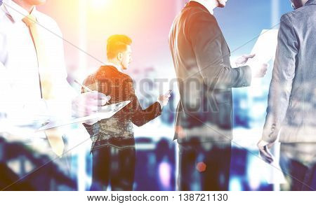 Business partners working on illuminated night city background with abstract sunlight. Teamwork and partnership concept. Double exposure