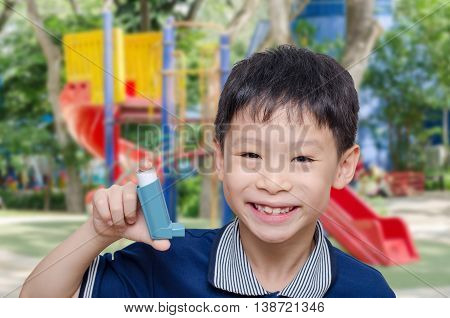 Asian boy holding inhaler and smiles at playground