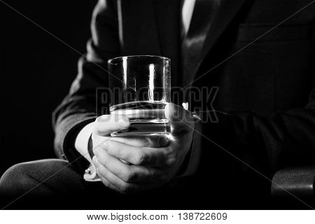 Closeup black and white picture of serious businessman holding whiskey illustrate executive privilege concept