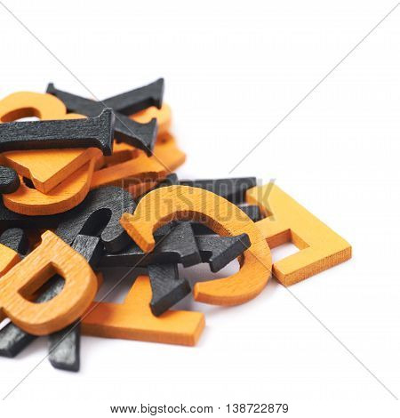 Pile of black and orange painted wooden letters isolated over the white background