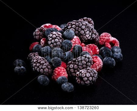forest fruits frozen raspberries blueberries and blackberries on a black stone table