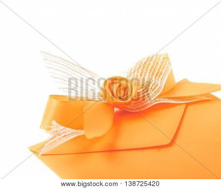 Paper envelope decorated with the bow isolated over the white background