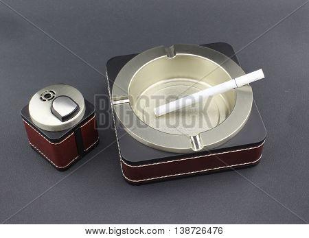 Cigarette in empty ashtray and cigarette lighter