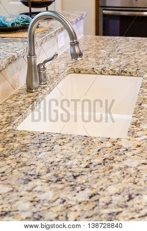 Modern Stainless Steel Faucet on Granite Kitchen Counter in New Home