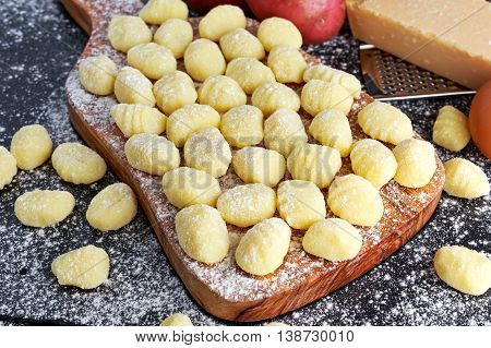 Uncooked homemade gnocchi on wooden cutting floured board
