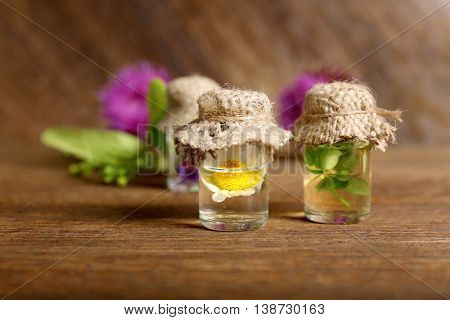 Chamomile in small glass bottle with hessian cap on wooden background