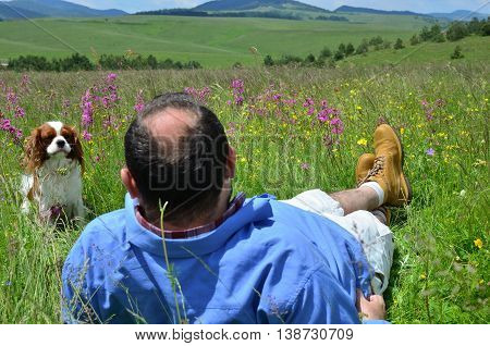 Man is resting on mountain field with his dog Cavalier King Charles Spaniel