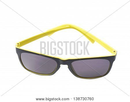 Pair of yellow plastic sunglasses with the dark shades, composition isolated over the white background