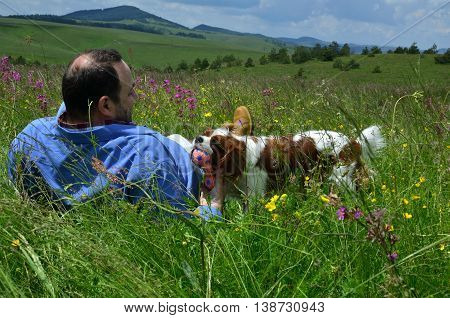 Man is lying on spring meadow and playing with his dog