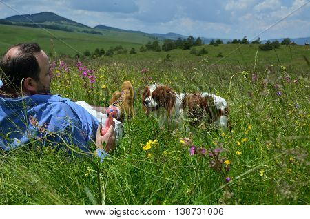 Man is lying on spring meadow and playing with his dog with toy for dogs