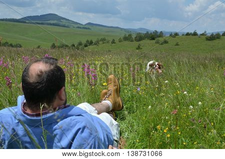 Man is resting on a spring mountain meadow and playing with his dog