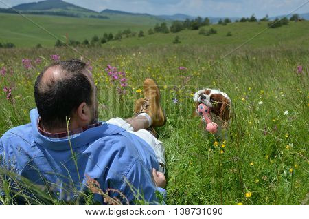 Dog is bringing toy for dogs to man resting on meadow