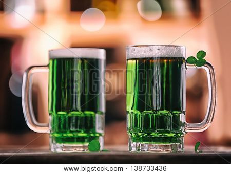 Glasses of green beer with clover leaves on blurred bar background