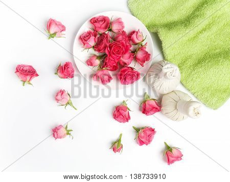 Spa settings with roses. Fresh roses in a plate and herbal compress using in spa treatments. Flat lay